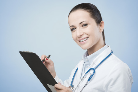 미소하고 의료 기록이 클립 보드 채 자신감을 여성 의사