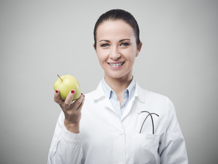 dietology: Smiling confident female nutritionist holding an apple
