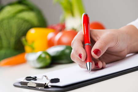 dietology: Nutritionist writing medical records and prescriptions with fresh vegetables