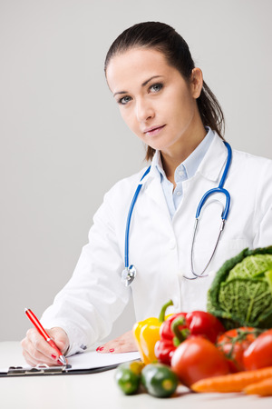dietitian: Smiling nutritionist writing medical prescriptions with fresh vegetables