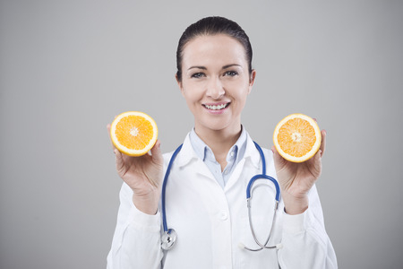 dietology: Smiling doctor showing a juicy orange, healthy eating concept