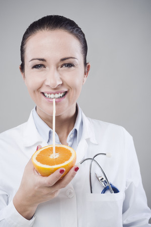 dietitian: Female doctor drinking orange juice directly from an orange using a straw