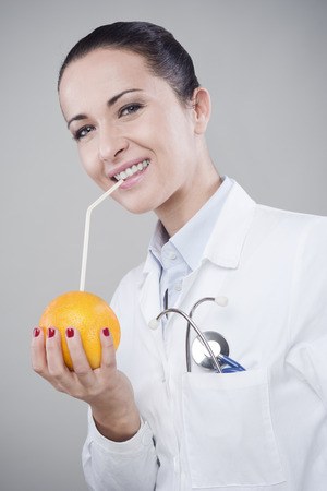 dietology: Female doctor drinking orange juice directly from an orange using a straw