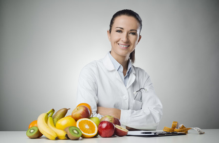 Confident nutritionist working at desk with fresh fruit Stock Photo
