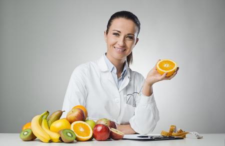 机に座っているとオレンジを保持している栄養士の笑みを浮かべてください。 写真素材