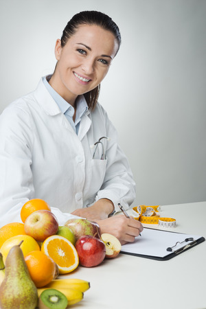 Smiling nutritionist writing medical records with fresh fruit on foreground
