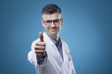 buena salud: Alegres que sonríen con los pulgares para arriba médico mirando a la cámara Foto de archivo