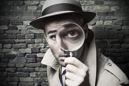 hombre con sombrero: Detective divertido vintage que mira a trav�s de una lupa Foto de archivo