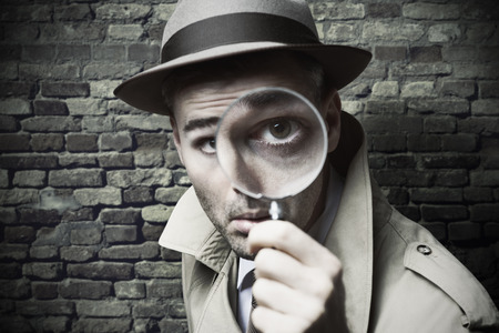 Divertente detective epoca guardando attraverso una lente di ingrandimento