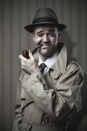 Detective divertido fumando una pipa y haciendo una cara extraña Foto de archivo