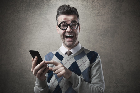 Cheerful funny guy holding a touch screen smartphone and staring with mouth open at camera