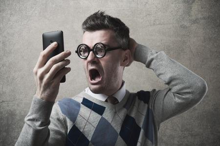 彼のスマート フォンでトラブルを抱えて面白い驚き怒っている男 写真素材