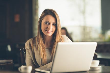 Mooie aantrekkelijke vrouw in het cafe met een laptop die een koffiepauze