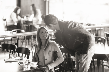 stylish boy: Beautiful smiling woman and stylish man meeting at the bar, he is touching her back Stock Photo