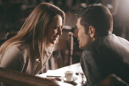 ロマンチックなカップルは、バーでお互いの目を見つめて