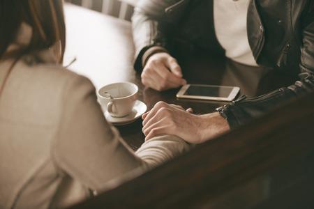 愛するカップルがバーで出会い、彼は彼女の手を握って、彼女の励み 写真素材