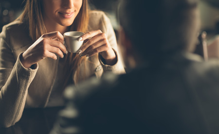mujer tomando cafe: Pareja de moda joven que data en el bar, que est� teniendo un caf� Foto de archivo