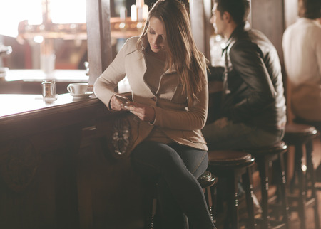 bar stool: Attractive woman sitting at the bar counter and texting with her mobile phone
