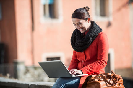 winter people: Smiling woman using her laptop in the street and connecting with a wi-fi connection Stock Photo