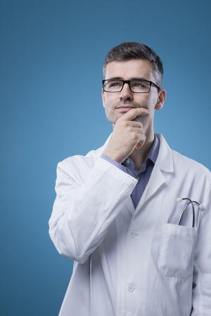 bata de laboratorio: Doctor pensativo con bata de laboratorio pensando con la mano en la barbilla Foto de archivo
