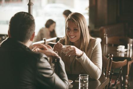 dos personas hablando: Pareja joven en el bar tomando un caf� y el coqueteo