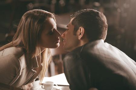 バーでキスする若いカップルのロマンスと愛の概念