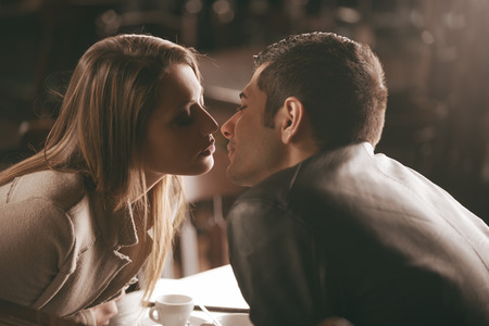Young couple kissing at the bar, romance and love concept Stock Photo