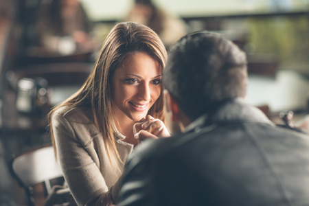 Romantic young couple dating and flirting at the bar, staring at each other's eyes