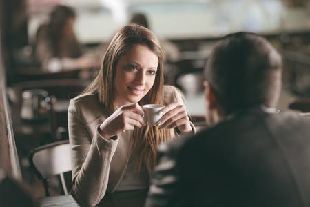 바에서 데이트하는 젊은 유행 부부, 그녀는 커피를 마시고있다