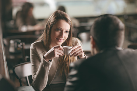 sitting pretty: Young fashionable couple dating at the bar, she is having a coffee Stock Photo