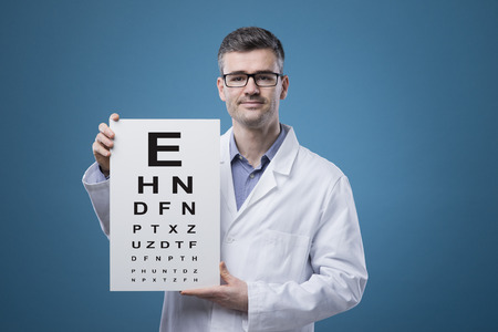 Professional optician holding an eye exam chart with letters Standard-Bild