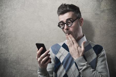wow: Individuo divertido que tiene problemas con su teléfono inteligente, la mano sobre la boca