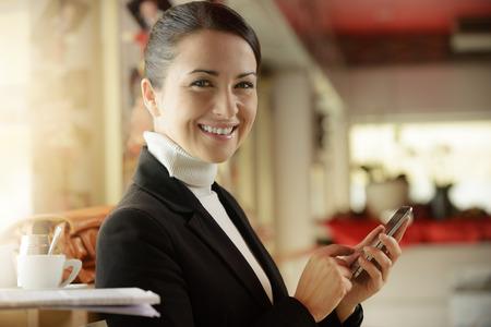 mujer elegante: Mujer elegante en la barra de mensajes de texto con su tel�fono m�vil de pantalla t�ctil