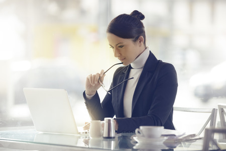 Occupato donna elegante al bar lavorando al suo computer accanto a una finestra