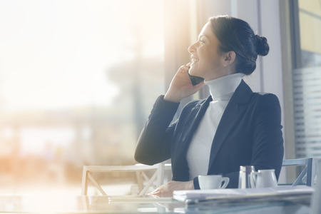 calling on phone: Smiling businesswoman on the phone having a break and drinking a coffee
