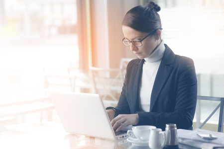 hot secretary: Confident businesswoman working on a laptop and having a coffee break