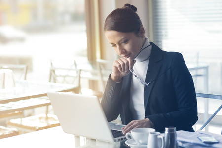 Confident smiling businesswoman working on a laptop and having a coffee break Stock Photo