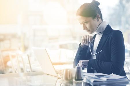 Drukke elegante vrouw aan de bar te werken op haar computer naast een raam