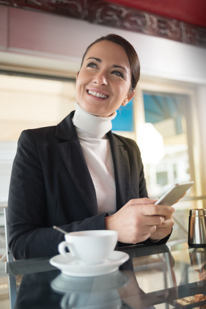 Woman having a coffee and chatting with her touch screen smart phone photo