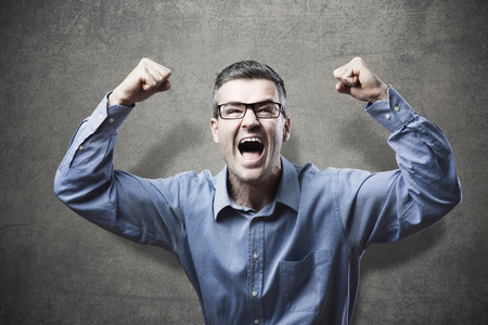 good news: Joyful businessman with fists raised receiving good news and shouting