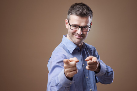smirking: Cheerful smirking businessman pointing at camera Stock Photo