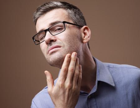 belleza masculina: Hombre en el espejo de comprobar la barba y la cara de la piel, el concepto de la belleza masculina