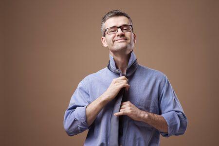 vistiendose: Hombre de negocios confidente vestirse y ajustando su nudo de corbata
