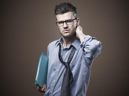 confundido: Empresario desordenado confuso con la mano detr�s de la cabeza, el desempleo y el concepto de la depresi�n Foto de archivo