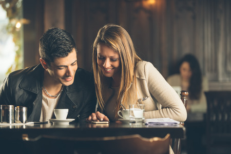 girlfriend: Cheerful friends at the cafe connecting to internet with a smart phone Stock Photo