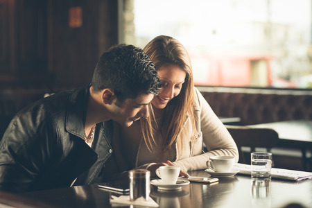 romance: Man and woman at the bar having a coffee and using a mobile phone Stock Photo
