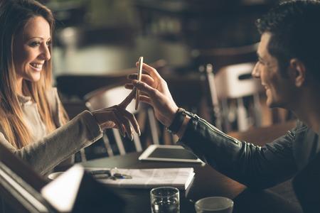 バーで若いおしゃれなカップル携帯電話タッチ スクリーンの携帯電話を使用して