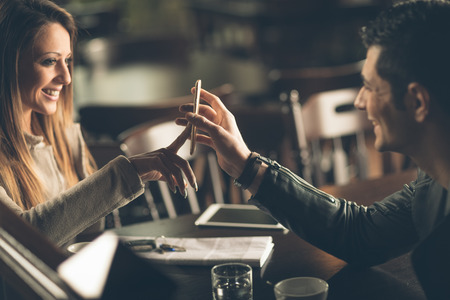pub: Young fashionable couple at the bar using a mobile touch screen phone