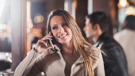 woman bar: Smiling young woman at the bar having a phone call with her mobile phone