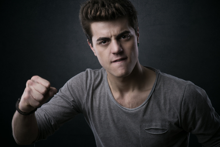 aggressive people: Young aggressive man showing fists and looking at camera